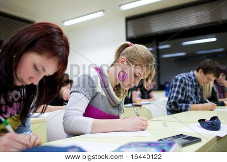pretty female college student sitting in a classroom full of students during class (shallow DOF; color toned image)