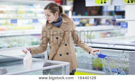hübsche junge Frau kaufen Lebensmittel in einem Supermarkt/Einkaufszentrum/Lebensmittelgeschäft (Farbe getönten; flach