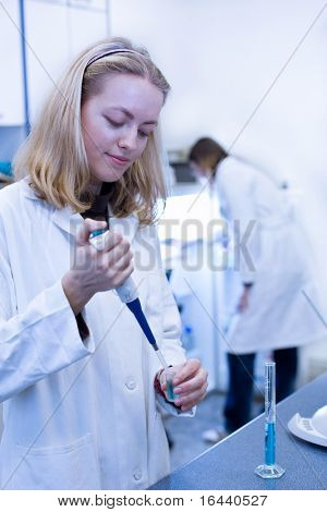 Closeup portrait of a female researcher carrying out experiments in a laboratory  (color toned image)