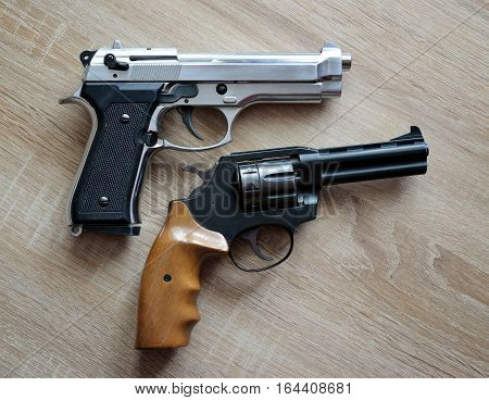 Two metallic pistols on a wooden board.