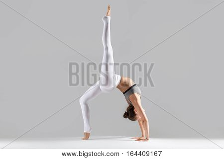 Young attractive woman practicing yoga, standing in Bridge exercise, One legged Wheel pose, working out wearing sportswear, white pants, indoor full length, isolated against grey studio background