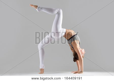 Young attractive woman practicing yoga, standing in Bridge exercise, One legged Wheel pose, working out wearing sportswear, bra, indoor full length, isolated against grey studio background