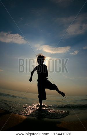 silhouette of boy playing in waves at a beach