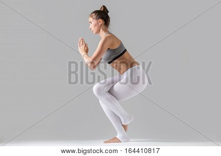 Young attractive woman practicing yoga, standing in Eagle exercise, Garudasana pose, working out wearing sportswear, white pants, gray top, indoor full length, isolated against grey studio background