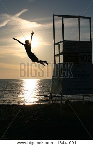 silhouette of boy jumping off lifeguard stand