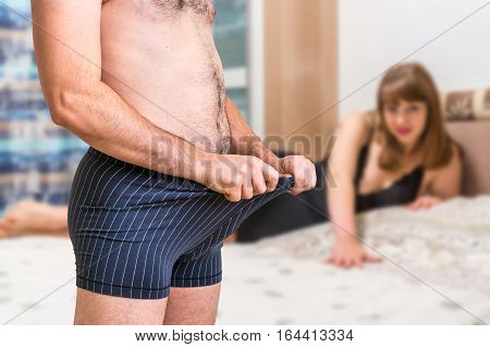 Woman In Bed And Man In Underwear Is Looking Inside