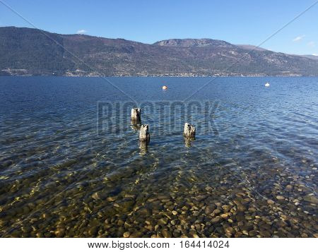Lake landscape view with three old wooden posts in shallow water. Pebble rocks in water and ripple waves.  Clear blue sky and mountains in background.