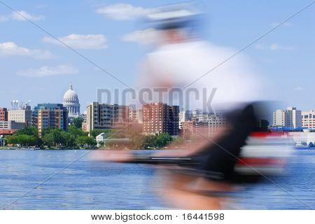 Bewegungsunschärfe einer Person mit dem Fahrrad vorbei an der Capitol City of Wisconsin in Madison