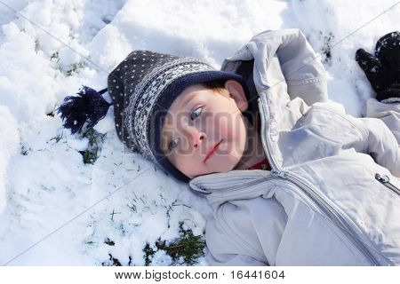 Boy resting after playing in the snow