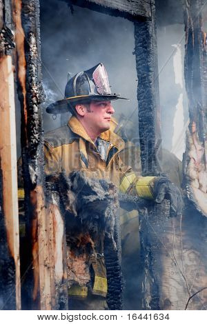 Firefighter looks out of a smoke filled house when the fire is under control