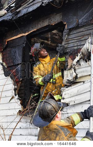Firefighter prying siding apart to stop a house from burning