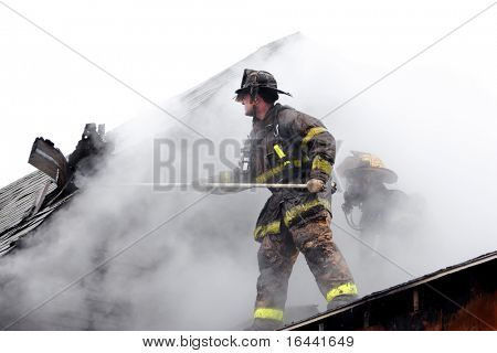 Firefighters on the roof of a house, prying up shingles to stop the fire from spreading