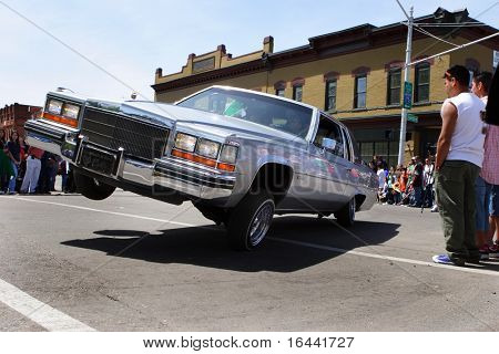 """Classic Lowrider performing a """"three wheel motion"""" in a Cinco de Mayo Parade in Detroit Michigan"""