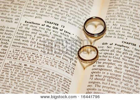 "Two wedding rings on a bible, open to Corinthians Chapter 13, ""The Gift of Love"""