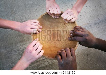 Hands holding an empty bowl, shallow depth of field focus on hands in foreground