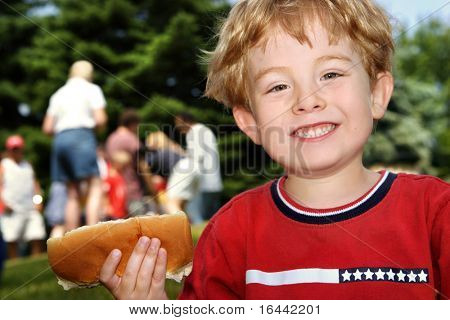 Boy holding a hot dog at a neighborhood picnic