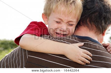 Young boy being comforted by his father