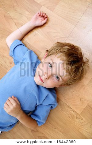 Serious boy laying on the floor