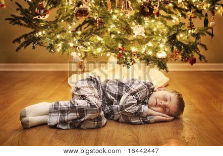 Young boy sleeping under the Christmas Tree waiting for Santa Claus to come