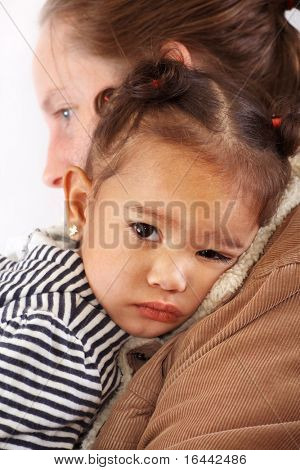 Young child comforted by her mother