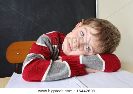 Child sitting at a desk laying his head on his arms