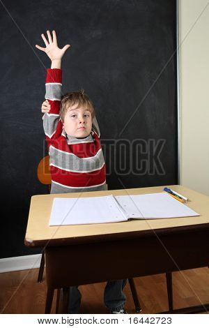 Young boy raising his hand in school