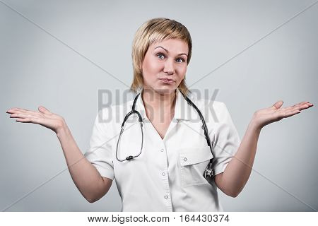 Smiling woman doctor shrugs shoulders over gray background