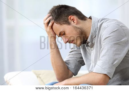 Side view of a sad man with a hand on the head sitting on a couch in the living room at home