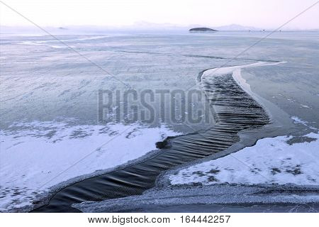 Strong wind breaks ice on water surface closeup view