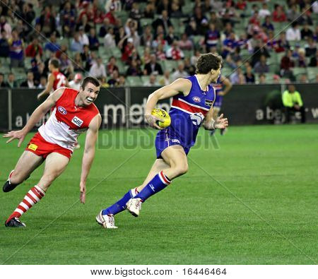 MELBOURNE - SEPTEMBER 12: Will minson burns off Darren Jolly in the AFL second semi final - Western Bulldogs vs Sydney Swans, September 2008
