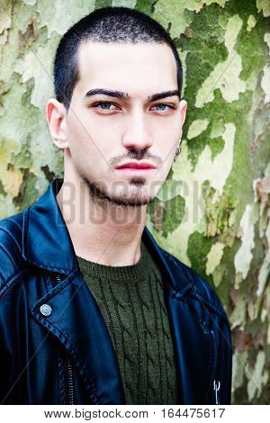 Portrait of a young handsome man near a tree. Tree with camouflage texture as background.