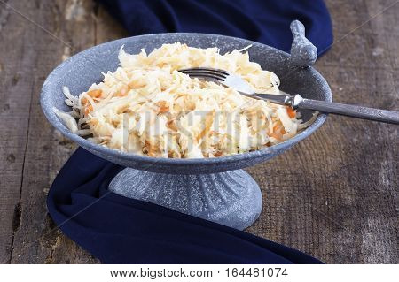Homemade Sauerkraut with carrots in an elegant stone plate with a bird on a rough wooden background with dark blue cloth. Traditional Ukrainian food.