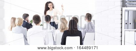 Young team leader giving a presentation to a group of employees