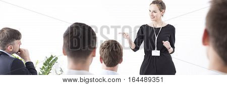 Young team leader pointing at somebody from the audience she is speaking to