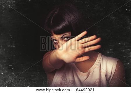 Refusing, stop violence against women. A young girl with her hand away and rejects violence of someone. Tears and crying. Black background. Focus on the face.