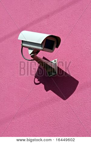 Security camera on bright pink wall