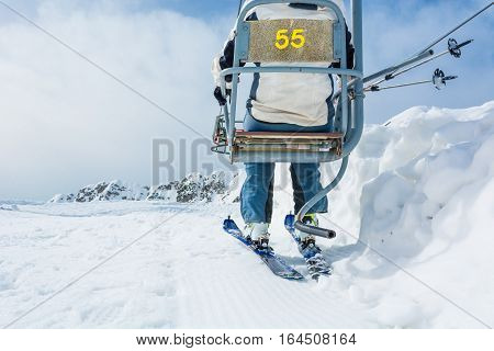 Back view of skier riding a lift. Skiing in the mountains.