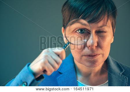 Female tax inspector with magnifying glass looking into papers and documents