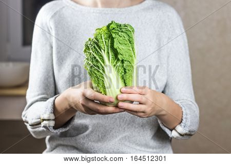 Chinese cabbage in female hands. Person holds napa cabbage in hands in home kitchen environment