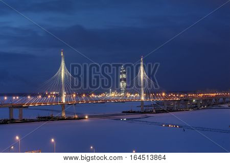 St. Petersburg Russia - January 2 2017: Western High-Speed Diameter with cable-stayed bridge across Petrovsky waterway and Gazprom tower under construction with night lighting in winter.