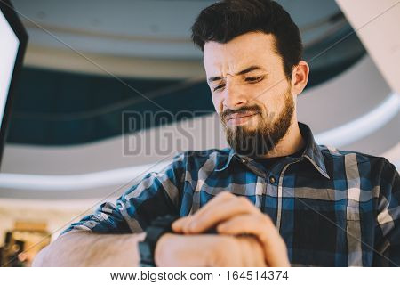 Serious man looking at his watch while standing on the urban background. Mad guy is checking the time and understanding he needs to cancell meeting. Close up