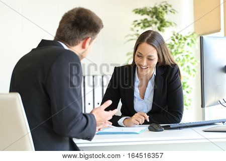 Salesclerk talking trying to convince to a happy client in a desktop at office