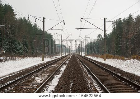 Straight railroad. Railway covered with snow. Forest.