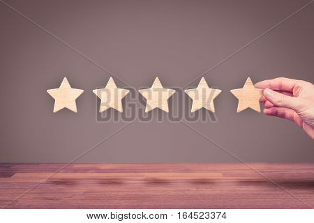 Increase rating, evaluation and classification concept. Businessman represented by his hand add fifth star.
