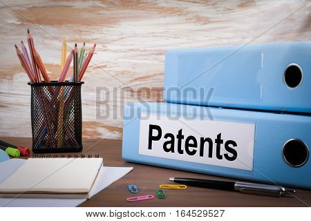 Patents, Office Binder on Wooden Desk. On the table colored pencils, pen, notebook paper.