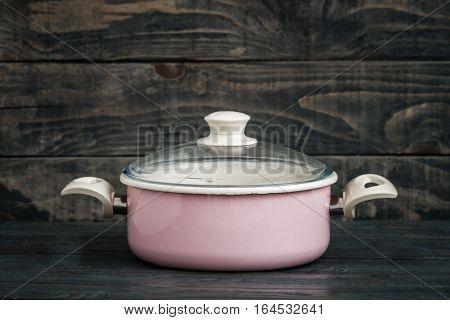 Vintage Style Pink Enamel Saucepan On Blue Wooden Background