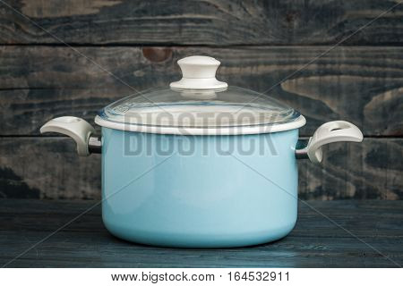 Vintage Style Blue Enamel Saucepan On Blue Wooden Background
