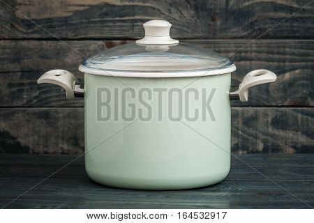 Vintage Style Green Enamel Saucepan On Blue Wooden Background