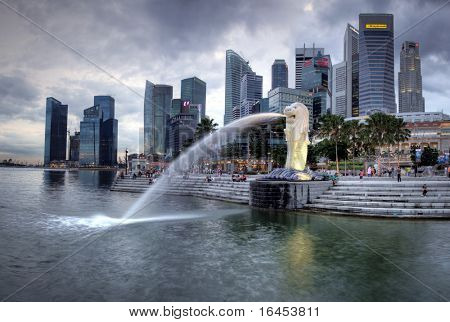 SINGAPORE-DEC 29: The Merlion fountain spouts water in front of the Singapore  skyline on Dec. 29, 2010.  Merlion is an imaginary creature with the head of a lion and the body of a fish and is often seen as a symbol of Singapore.