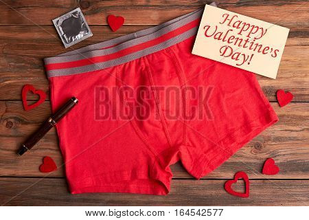 Boxer briefs and condom. Valentine's Day card, pen, hearts. Hot celebration of winter holiday.